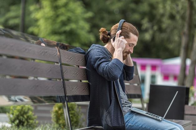 Вид сбоку человека на скамейке в городе с ноутбуком Бесплатные Фотографии