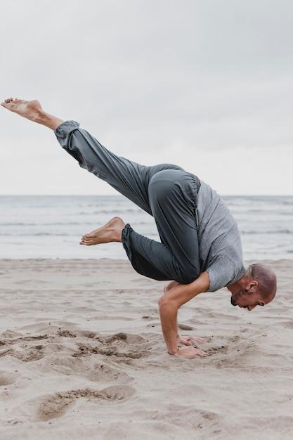 Вид сбоку человека на пляже, практикующего позы йоги Бесплатные Фотографии