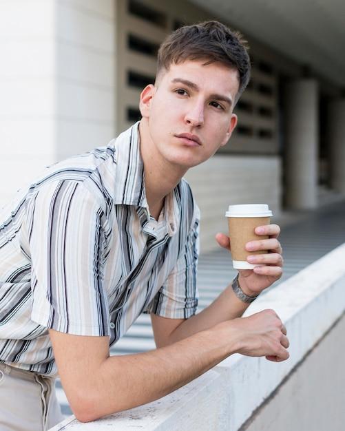 Вид сбоку человека, позирующего на открытом воздухе с кофе Бесплатные Фотографии