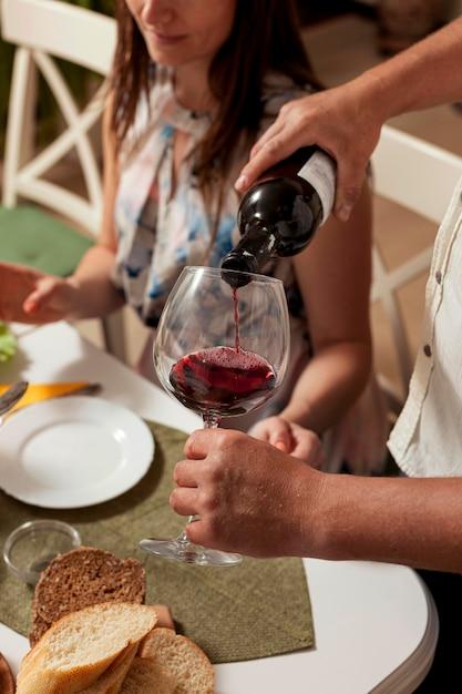 夕食の席でグラスにワインを注ぐ男の側面図 無料写真