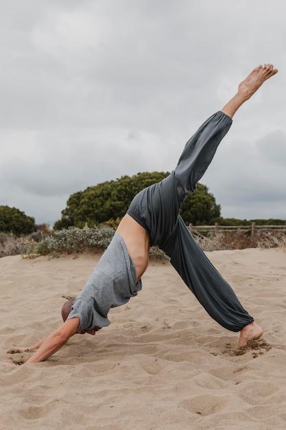 Вид сбоку человека, практикующего йогу на открытом воздухе Бесплатные Фотографии