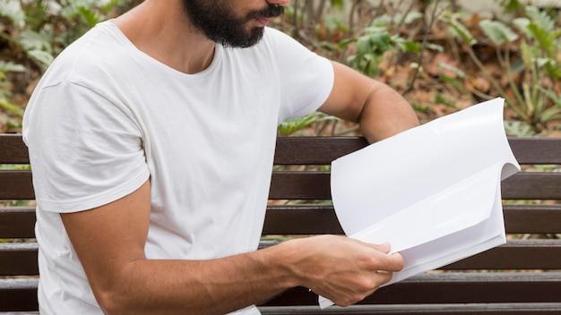 ベンチで本を読んでいる男の側面図 無料写真
