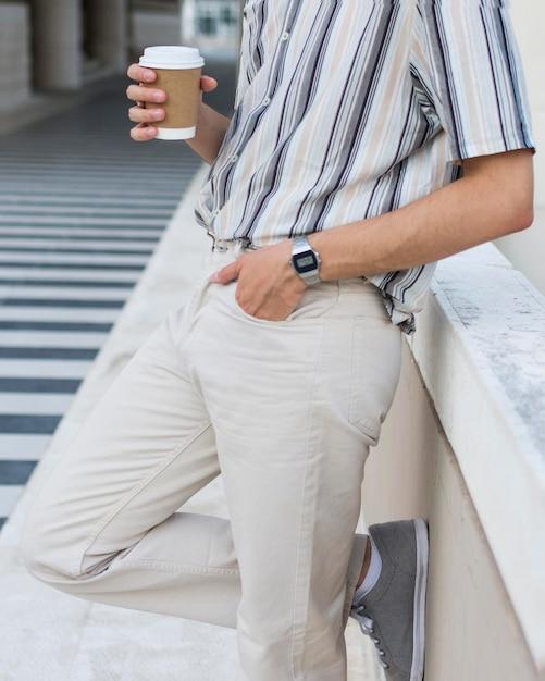 Вид сбоку человека, расслабляющегося на открытом воздухе с кофе Бесплатные Фотографии