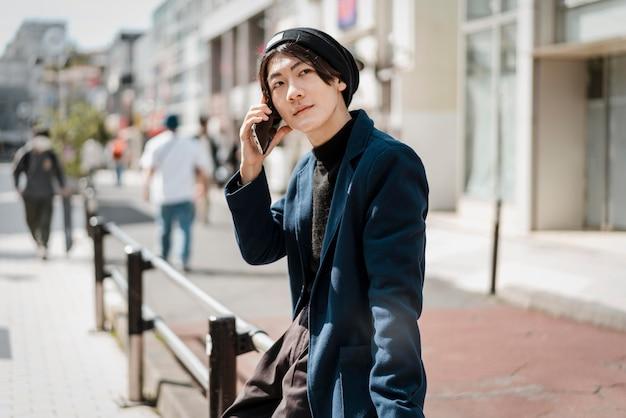 Вид сбоку человека, сидящего на перилах и разговаривающего по телефону Бесплатные Фотографии