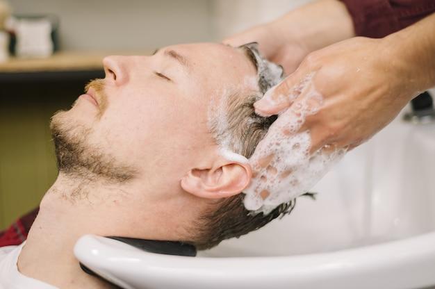 Вид сбоку человека, мытье волос в парикмахерской Premium Фотографии