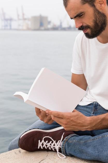 湖のほとりで本を読んで髭を持つ男の側面図 無料写真