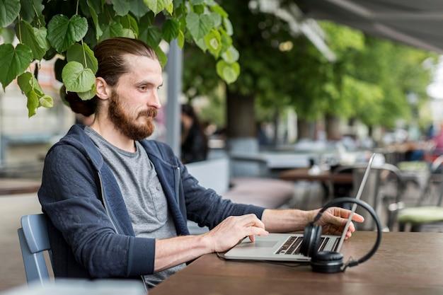 Вид сбоку человека с ноутбуком и наушниками на городской террасе Бесплатные Фотографии