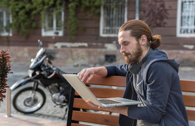 Вид сбоку человека с ноутбуком в городе Бесплатные Фотографии