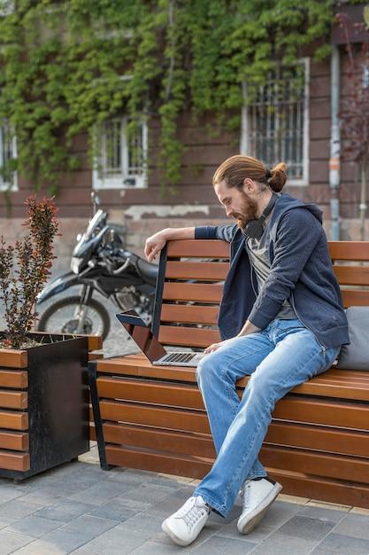Вид сбоку человека с ноутбуком на улице в городе Бесплатные Фотографии