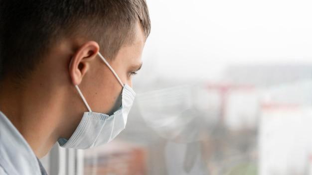 Вид сбоку на человека с медицинской маской, смотрящего в окно Бесплатные Фотографии