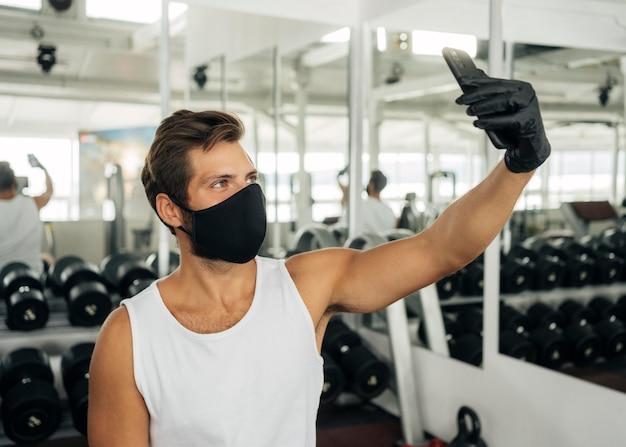 ジムで自分撮りをしている医療マスクを持つ男の側面図 Premium写真