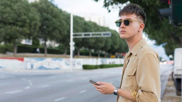 Вид сбоку человека в солнцезащитных очках в городе, держащего смартфон Бесплатные Фотографии
