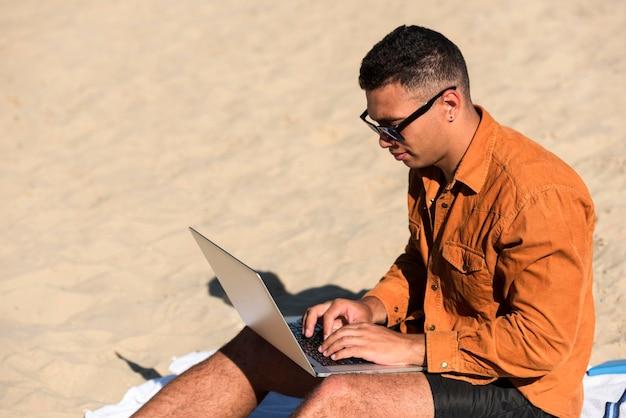 Вид сбоку человека, работающего на ноутбуке на пляже Бесплатные Фотографии