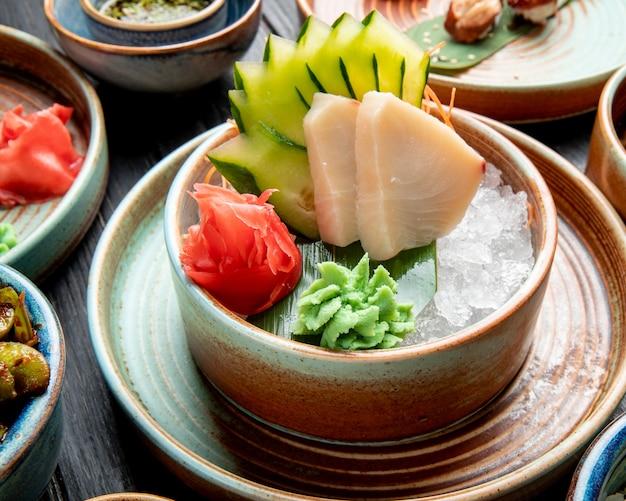 テーブルの上の皿にアイスキューブにスライスしたキュウリの生姜とわさびソースのニシンフィレのマリネの側面図 無料写真