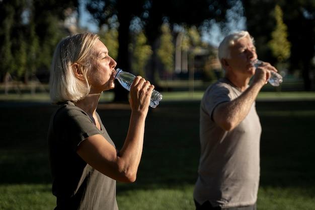 Вид сбоку зрелой пары питьевой воды снаружи Бесплатные Фотографии