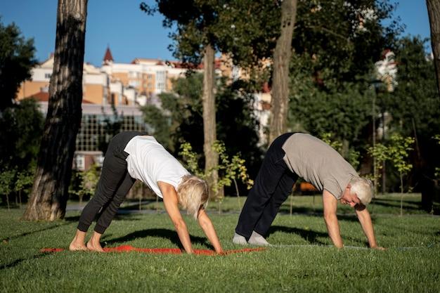 Вид сбоку зрелой пары, практикующей йогу на открытом воздухе Бесплатные Фотографии