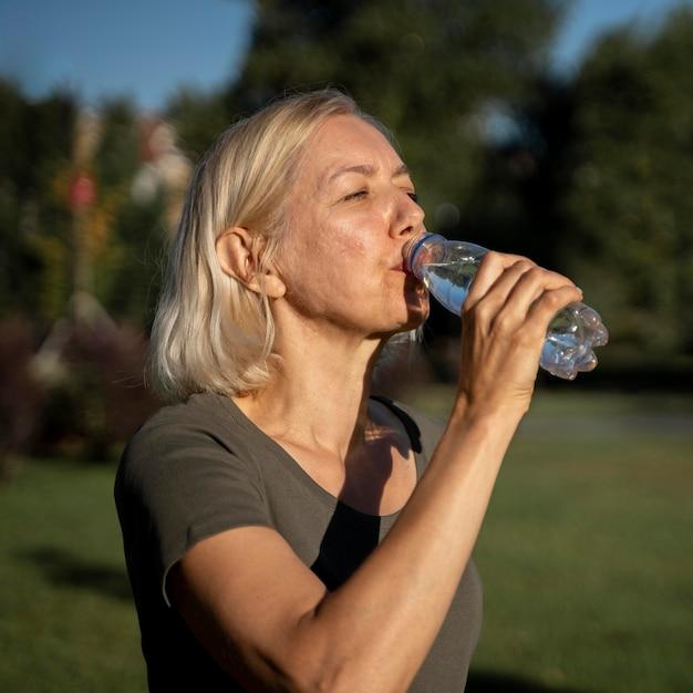 Вид сбоку зрелой женщины питьевой воды на открытом воздухе Бесплатные Фотографии