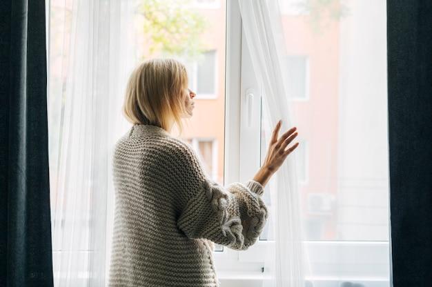 창을 통해 보는 대유행 동안 집에서 우울한 여자의 측면보기 무료 사진