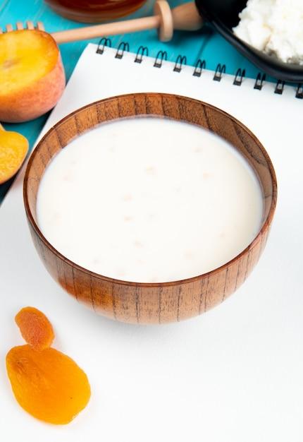 スケッチブックとドライアプリコットブルーの熟した桃の木製ボウルにミルクの側面図 無料写真