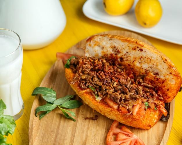 Вид сбоку фарша с овощами в хлебе, подается со свежими помидорами и лимоном на деревянной доске Бесплатные Фотографии