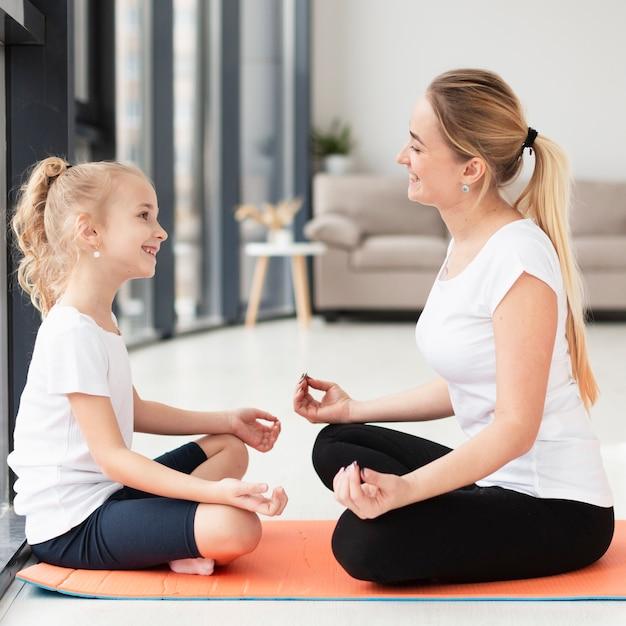 Взгляд со стороны матери и дочери делая представление йоги дома Бесплатные Фотографии