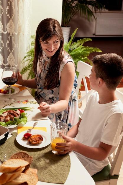 Вид сбоку матери и сына за обеденным столом Бесплатные Фотографии