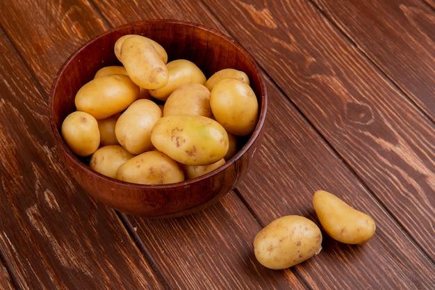 Вид сбоку нового картофеля в миску на деревянный стол Бесплатные Фотографии