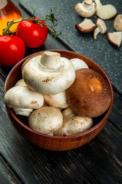 Вид сбоку свежих грибов в деревянной миске и свежих помидоров на черном Бесплатные Фотографии