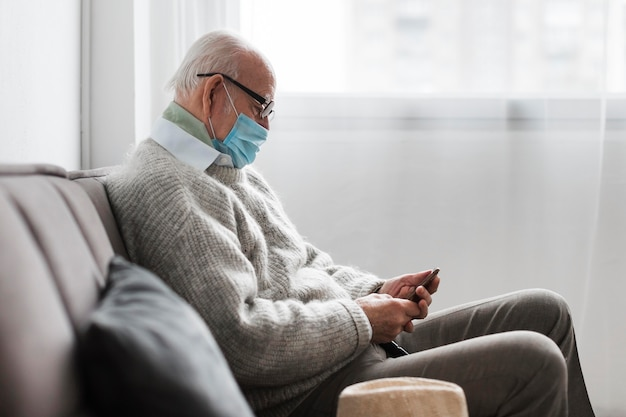 Вид сбоку на старика с медицинской маской в доме престарелых с помощью смартфона Premium Фотографии
