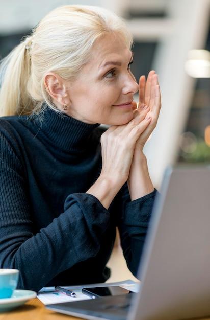 Вид сбоку пожилой деловой женщины, работающей на ноутбуке, наслаждаясь кофе Бесплатные Фотографии