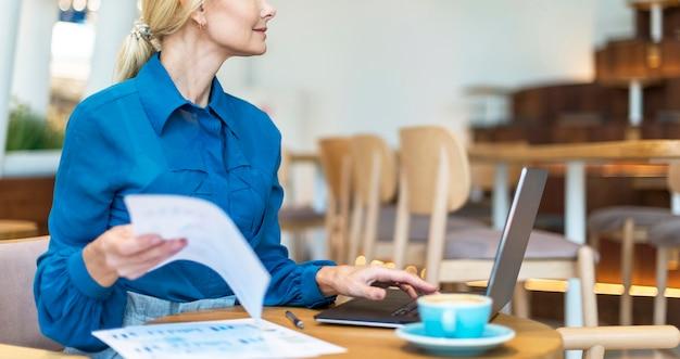 Вид сбоку пожилой деловой женщины, работающей на ноутбуке за чашкой кофе Бесплатные Фотографии