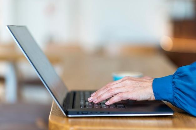 Вид сбоку пожилой деловой женщины, работающей на ноутбуке Бесплатные Фотографии