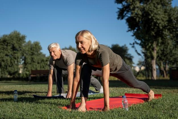 Вид сбоку пожилой пары, практикующей йогу на открытом воздухе Бесплатные Фотографии