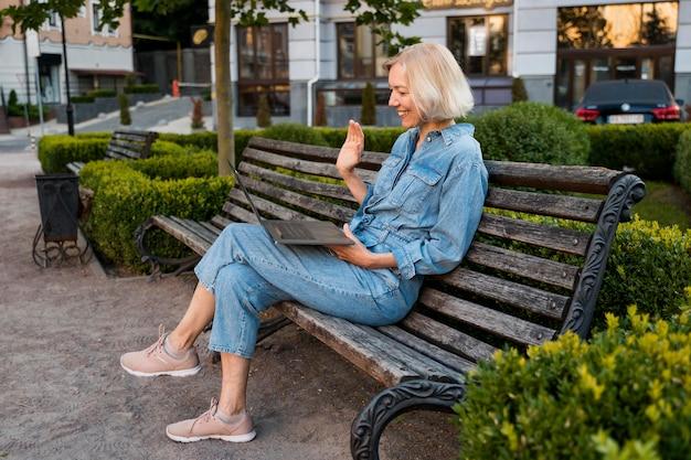 Вид сбоку пожилой женщины на открытом воздухе на скамейке, размахивая ноутбуком Бесплатные Фотографии