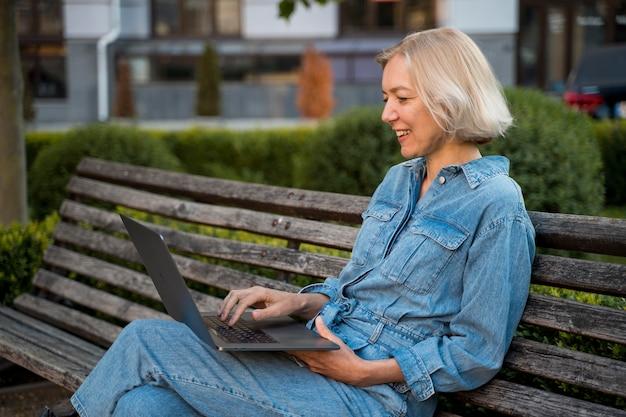 Вид сбоку пожилой женщины на открытом воздухе на скамейке с ноутбуком Premium Фотографии