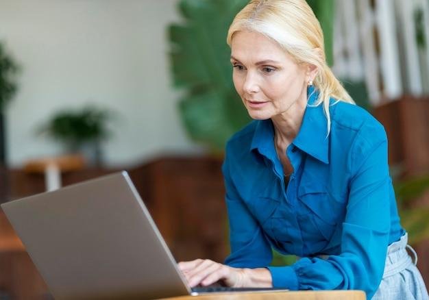 Вид сбоку пожилой женщины, работающей на ноутбуке во время отсутствия Бесплатные Фотографии
