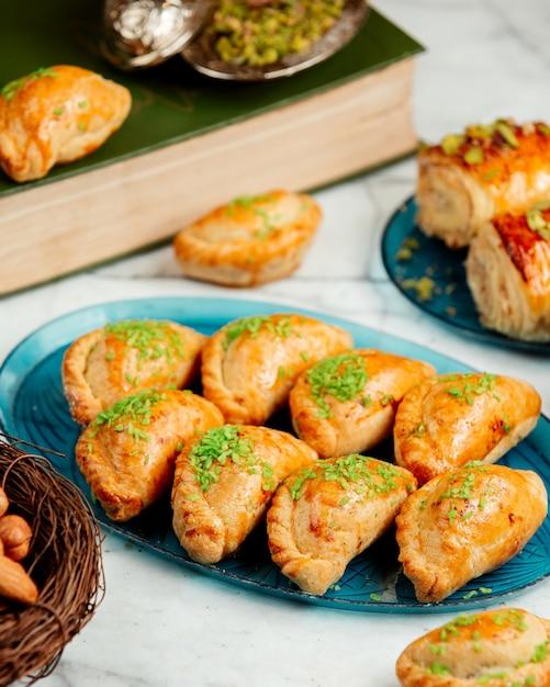 Вид сбоку восточного теста с орехами и фисташками на блюде Бесплатные Фотографии