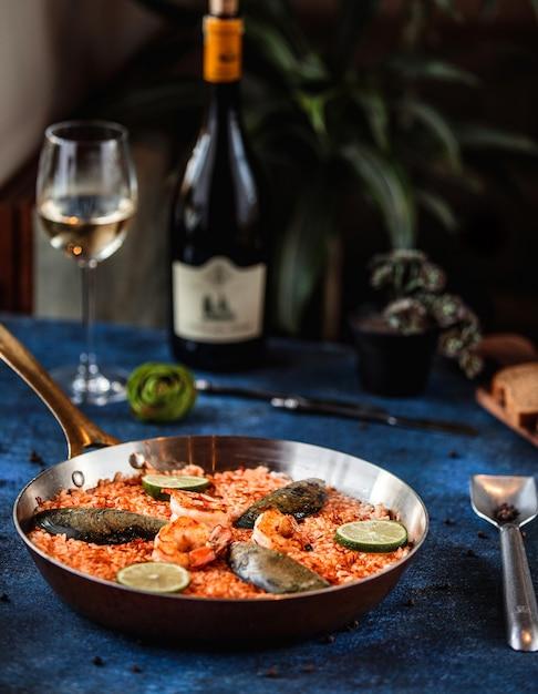 Вид сбоку паэлья с мидиями и креветками в сковороде на синем Бесплатные Фотографии
