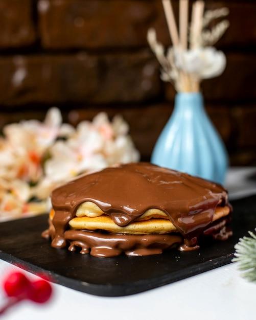 Вид сбоку блины с шоколадным маслом на деревянной разделочной доске Бесплатные Фотографии