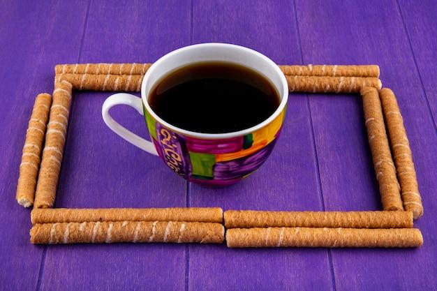 紫色の背景の中心に一杯のコーヒーと正方形のクリスピースティックセットのパターンの側面図 無料写真