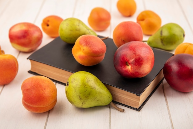 閉じた本と木製の背景に桃と梨のような果物のパターンの側面図 無料写真