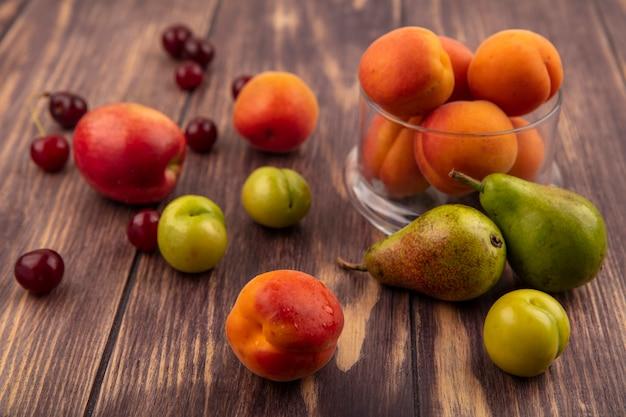 木製の背景に桃チェリープラム梨とアプリコットの瓶として果物のパターンの側面図 無料写真