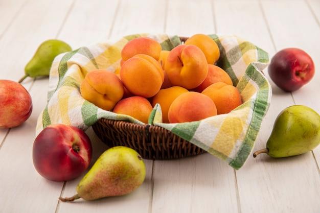 Вид сбоку персиков в корзине с грушами на деревянных фоне Бесплатные Фотографии