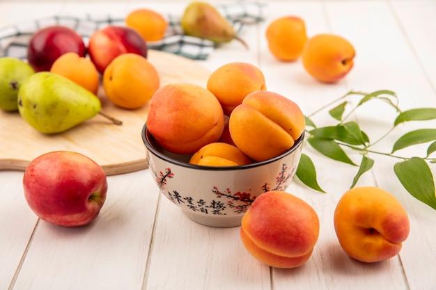 Вид сбоку персики в миске и груши с персиками на разделочной доске и листьями на деревянном фоне Бесплатные Фотографии