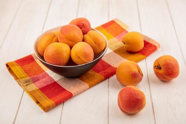 格子縞の布と木製の背景のボウルに桃の側面図 無料写真