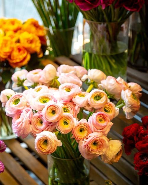 フラワーショップでガラスの花瓶にピンクのラナンキュラスの花の花束の側面図 無料写真