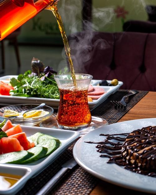 Вид сбоку наливания черного чая в стакан armudu Бесплатные Фотографии