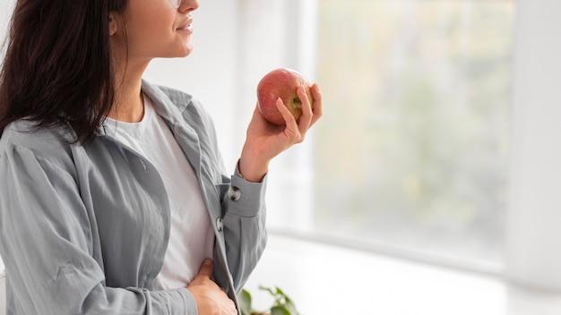 Вид сбоку беременной женщины, держащей яблоко с копией пространства Бесплатные Фотографии