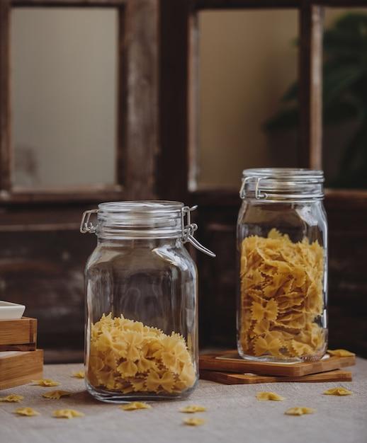 Вид сбоку сырой фарфалле макароны в стеклянных банках на деревянном столе Бесплатные Фотографии