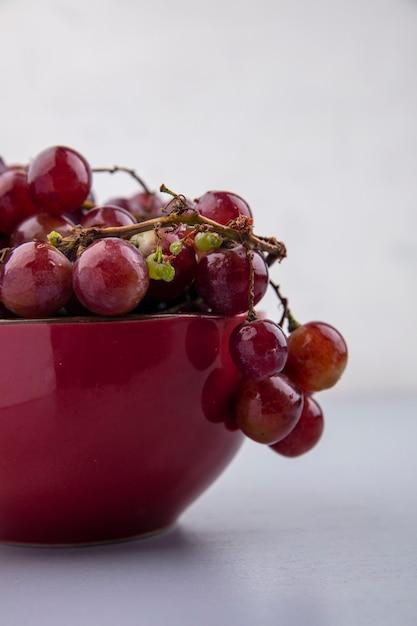 灰色の背景の格子縞の布のボウルに赤ブドウの側面図 無料写真